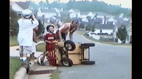 Helmeted Kids In Red Wagon Crash Into Sidewalk And Go Flying