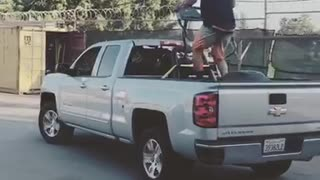 A man on a treadmill on the back of a silver truck - Video
