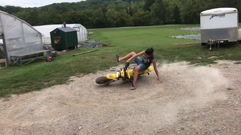 Woman on yellow dirt bike spins and falls
