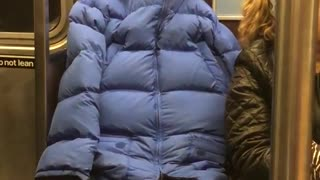 Person subway blue puffy jacket tied holes covered