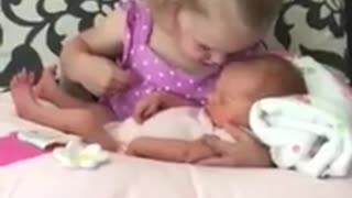 Little girl preciously watches over newborn baby sister