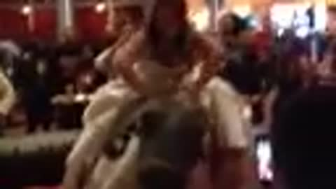 Bride rides mechanical bull in wedding gown