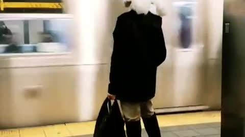 Woman wears a large feather hat at subway station