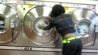 Woman Opens Washing Machine At Laundromat Mid-Cycle - Video