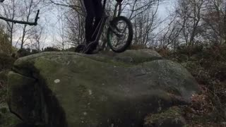 Guy tries to drive over rocks on bike falls forward into bush - Video
