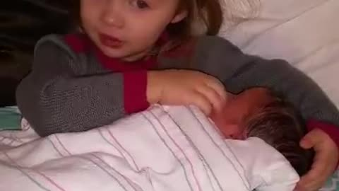 "Big sister singing "" Baby Mine"" to newborn baby brother"