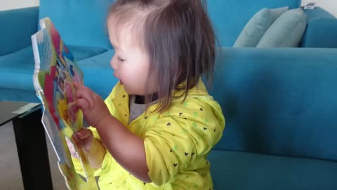 Toddler reads English book in native tongue