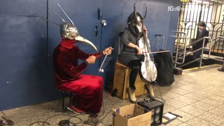 Two people in silver masks playing instruments