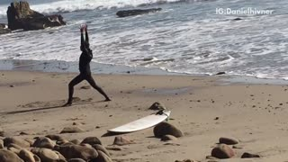 Guy filmed doing karate poses next to board on beach - Video