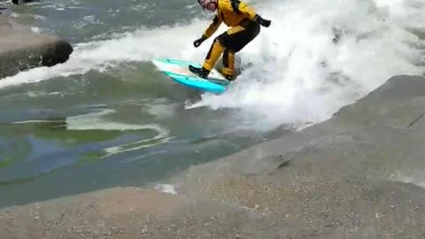 Guy yellow suit river surfing
