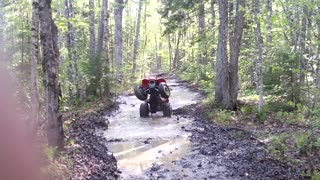 Red quad stuck river revs falls back - Video