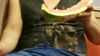 Man on train eating half watermelon
