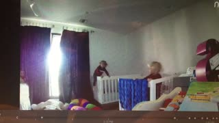 Blonde baby in red climbs out of white crib camera