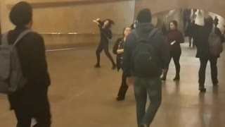 Woman in black outfit dancing in train station