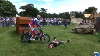 Motorcycle trials rider stunts over brave volunteer