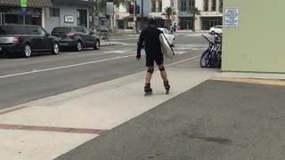 Guy on rollerblades with surfboard  - Video