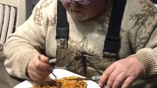 Man uses scissors to make eating spaghetti easier