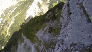 Wingsuit flying along mountainside cliff - Video