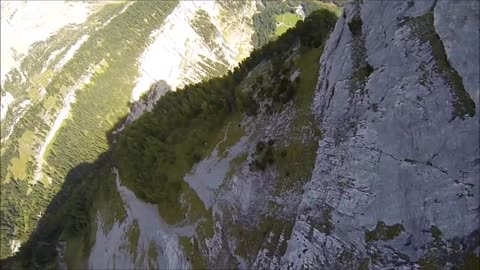 Wingsuit flying along mountainside cliff