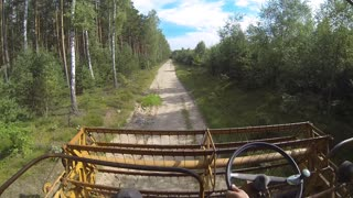 Farmer drives through the forest by harvester  - Video