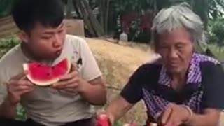 an  eating watermelon competition between grandma and grandson.  - Video