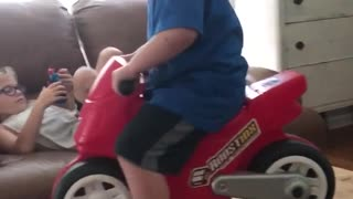 Little boy blue shirt red motorcycle falls off table