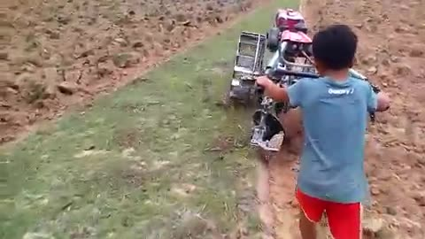 A cute kid is doing cultivation with hand machine very technic