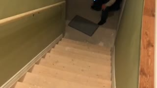 Guy slides down stairs with towel cape - Video