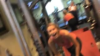 Girl in a pink top at a gym falls after lifting heavy weight