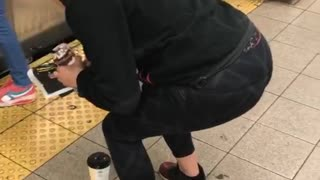 Girl frozen squatting in front of coffee in front of subway