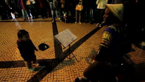 Baby walks up to street performer, steals the show!