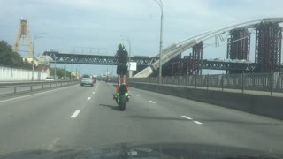 Man Rides Motorcycle Standing Up in Traffic - Video