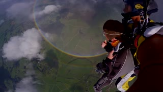 Skydivers soar above 360 degree double rainbow - Video