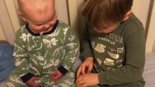 Big brother reads to little brother in his crib