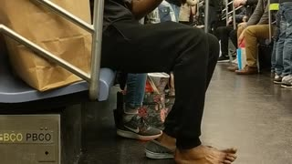 Shoeless man purells hands and feet on subway