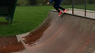 Blue jacket orange shoes girl slips on skateboard half pipe - Video