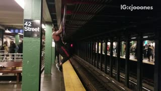Pt. 2 guy wearing headphones and tank top works out in subway station pull ups