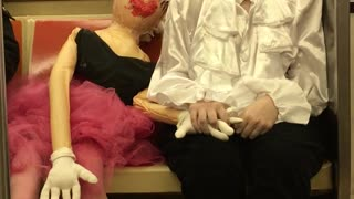 Girl dressed as a mime holds hands with a mannequin doll on subway train