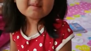 Cute indian Girl eating sour fruit