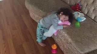 Little girl falls asleep in upright position
