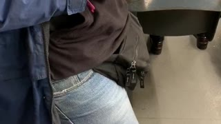 Guy fiddles with handcuffs on subway train