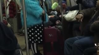 Guy on subway wears blue fur coat and white polka dot shorts - Video