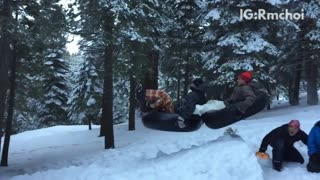 Guys on snow tube sliding down hill and hitting tree