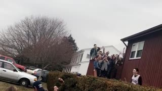 Guy jumps off roof of beige house - Video