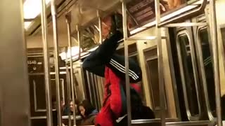 Man in spiderman outfit hangs from subway ceiling