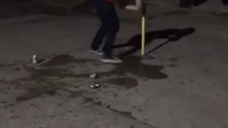 Guy red shirt spinning in circles playing dizzy bat - Video