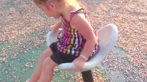 Little girl on white spinning chair at park spins too much and falls off