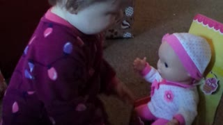 Playful baby has precious reaction to new doll
