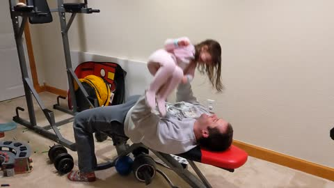 Dad gets creative by bench pressing daughter in home gym