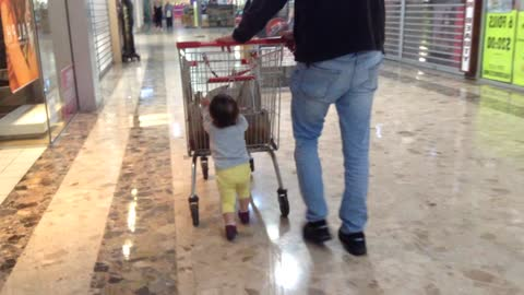 Toddler adorably helps daddy push cart